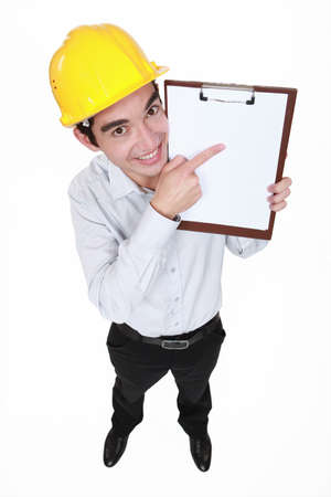 Happy man pointing at clip board photo
