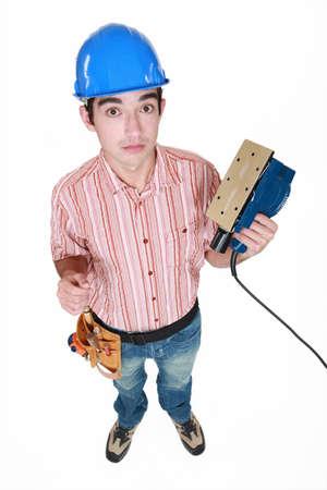 sander: Construction worker holding a sander.