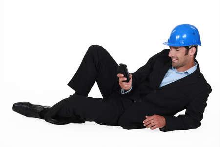 creador: Arquitecto tirado en el piso con el móvil