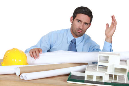 exasperate: architect in his office looking angry