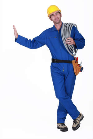 cabling: Electrician carrying spool of cable