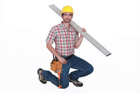 kneel down: portrait of handsome carpenter against white background carrying steel post