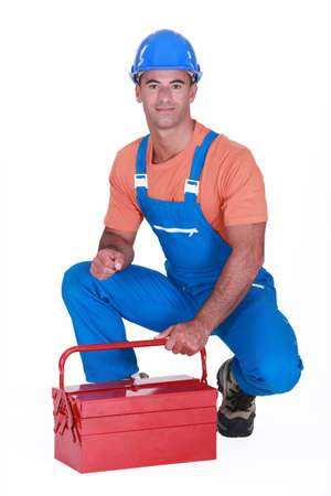 studio happy overall: craftsman squatting with toolbox Stock Photo