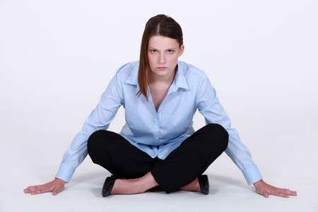 Stern businesswoman sitting cross legged