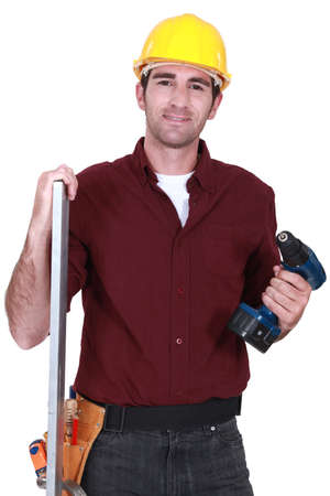 Builder posing with drill and plank photo