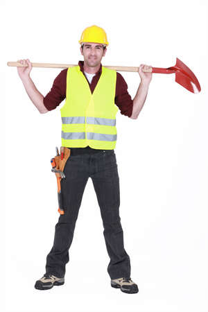 legs apart: full-body portrait of bricklayer standing legs apart carrying shovel on his shoulders Stock Photo