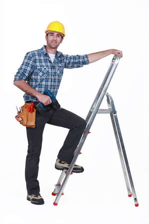 rungs: Man with drill climbing ladder Stock Photo