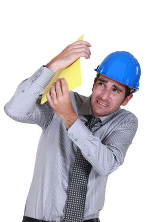 alarmed: Engineer shielding himself from a blow Stock Photo