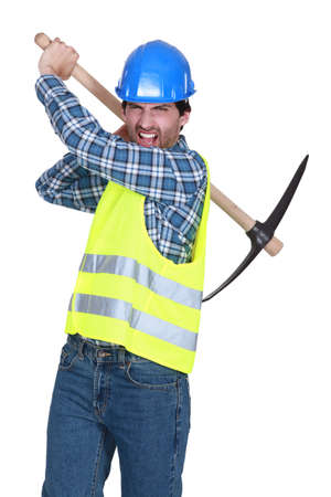 pointed arm: Aggressive labourer holding a pickaxe Stock Photo