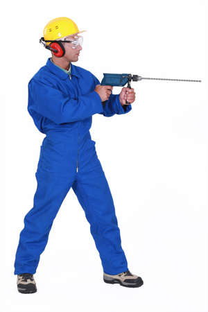 Man drilling through wall Stock Photo - 16779217