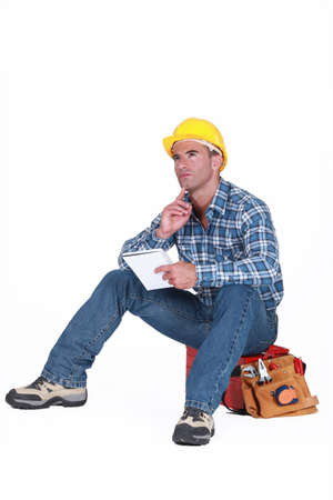 Builder sat on tool box thinking Stock Photo - 16779347