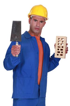 stonemasonry: Angry tradesman holding a brick and trowel