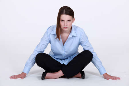forbidding: Stern businesswoman sitting cross legged