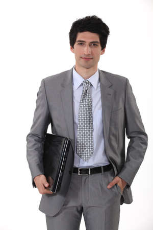 Smart businessman carrying laptop photo