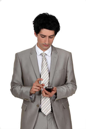 downcast: handsome businessman holding cell phone with downcast eyes Stock Photo