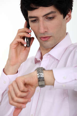 A businessman over the phone looking at his watch  photo