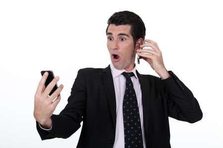 surprised man: businessman holding two cell phones