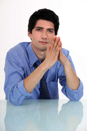 circumspect: Businessman with his hands pressed together