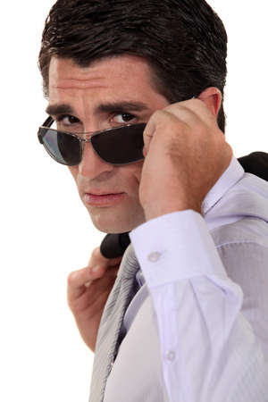 Businessman peering over his sunglasses Stock Photo - 16808197