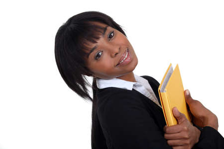 tilted: Businesswoman hugging a folder to her chest