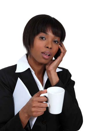 Businesswoman with mug of coffee and telephone Stock Photo - 16807607