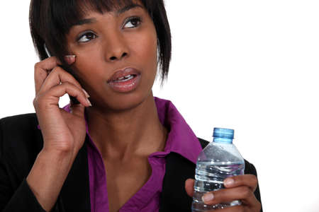 A black businesswoman on the phone waiting to take a sip Stock Photo - 16807757