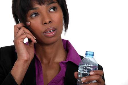 sorbo: Una mujer de negocios negro en el tel�fono esperando para tomar un sorbo Foto de archivo