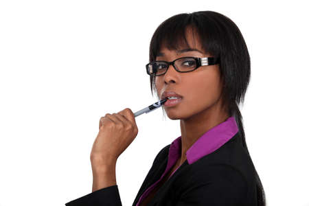 reconsider: Businesswoman chewing on her pen Stock Photo
