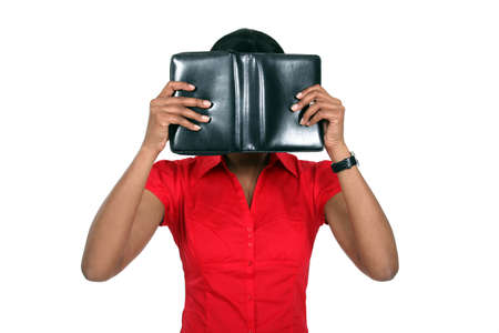 Woman hiding her face behind a leather-bound book photo