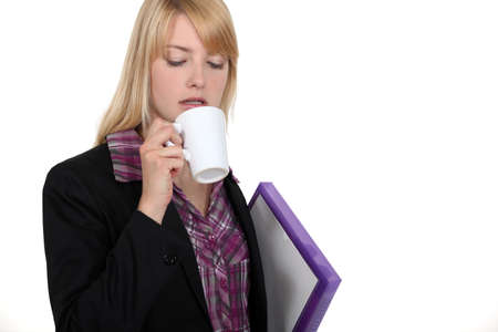 Blond worker carrying folder and coffee Stock Photo - 16806002