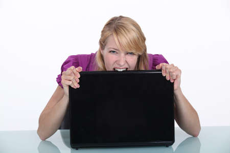 insane insanity: Woman biting her laptop Stock Photo