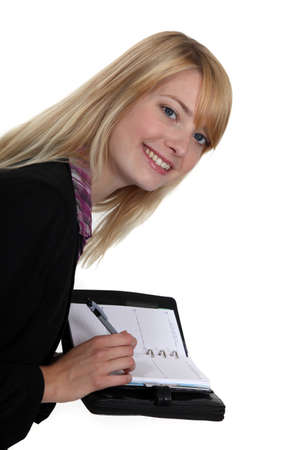 Blond woman writing in her agenda photo