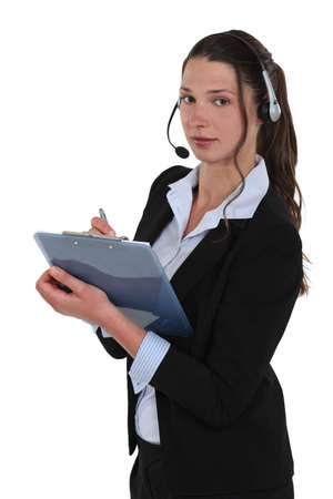 Brunette call-center worker writing on clip-board Stock Photo - 16806579