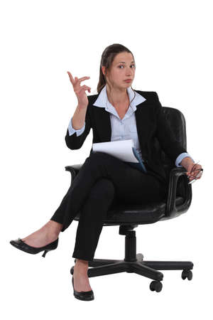 A businesswoman seated on a chair  Stock Photo - 16805336