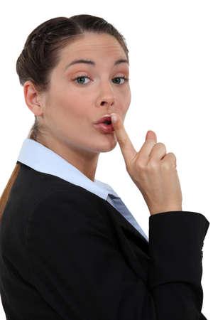 shushing: A businesswoman shushing  Stock Photo