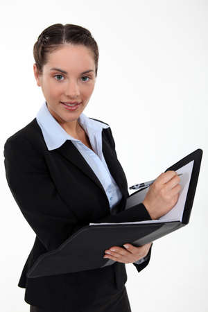 Beautiful woman holding a clipboard and a pen photo