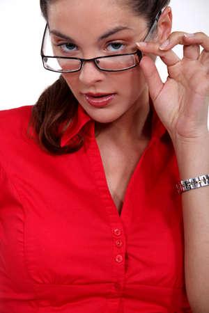 Businesswoman peering over her glasses photo