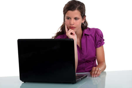 inconclusive: Pensive woman staring at her laptop