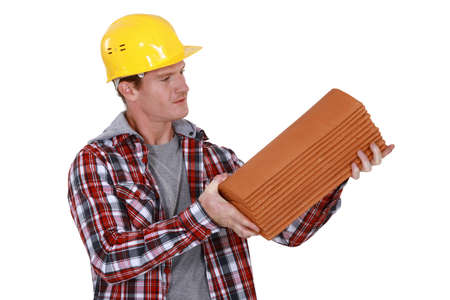 Roofer holding pile of tiles photo