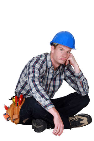 plumbing tools: Bored builder sat on the floor