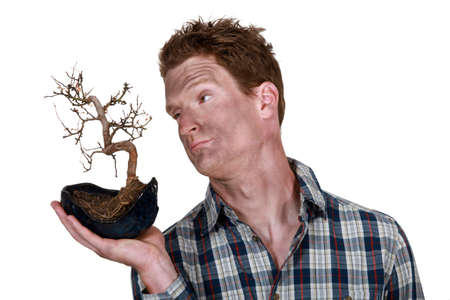affliction: man covered with dirt holding a dead plant Stock Photo