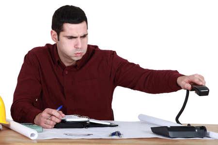 directorio telefonico: Hombre tensionado colgar el teléfono Foto de archivo