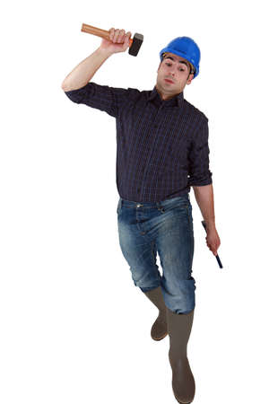 Builder lifting hammer over head Stock Photo - 16890047
