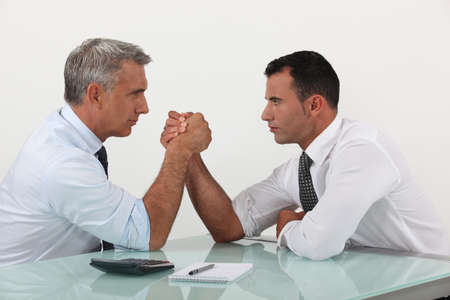 competitors: Businessmen arm wrestling Stock Photo