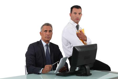 Two businessmen sat at desk Stock Photo - 16889999