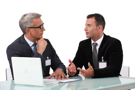 insist: Men chatting at a desk