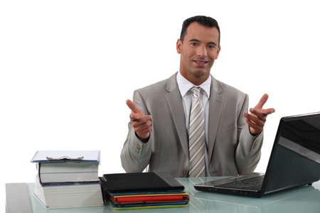 Arrogant businessman sat at desk photo