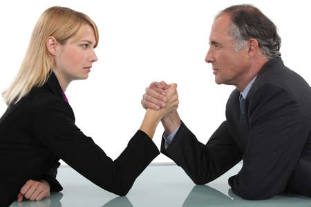 Businessman and woman arm wrestling photo