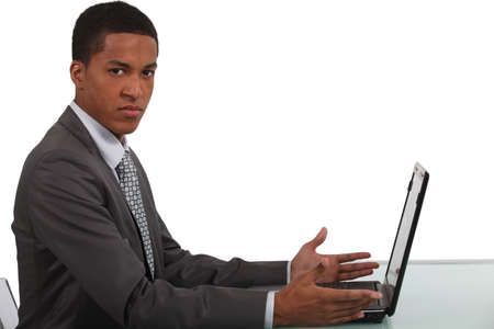 Disgruntled office worker sat with laptop Stock Photo - 16888753