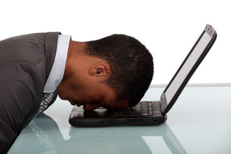 exhausted businessman sleeping over his laptop